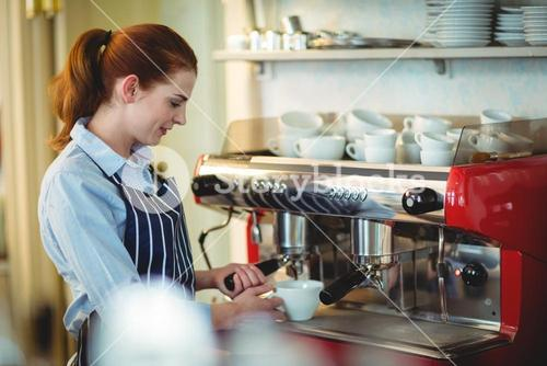 Young waitress using coffee maker at cafeteria