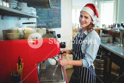 Portrait of happy waitress wearing Santa hat at cafe