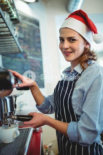 Portrait of waitress using coffee maker at cafeteria during Christmas