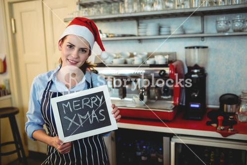 Portrait of barista holding Christmas sign at cafe