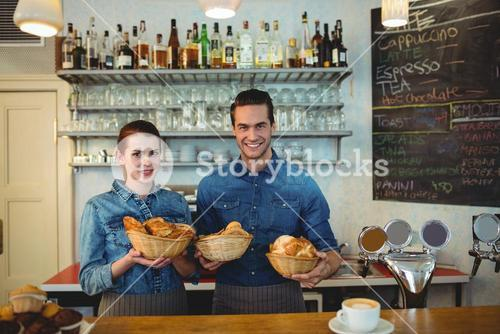 Portrait of happy co-workers with breads at cafe