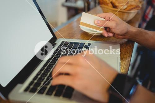 Close-up of customer spending money on online at cafe