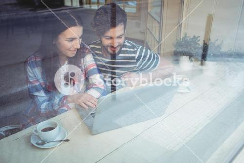 Couple using laptop with coffee at cafe