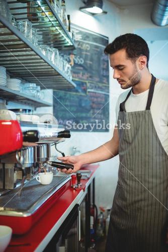 Waiter using espresso maker at coffee house