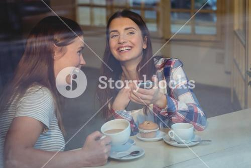 Cheerful women with cellphone at coffee shop