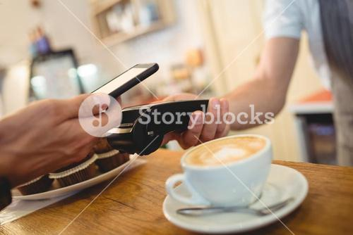 Close-up of customer with cellphone and barista with card reader