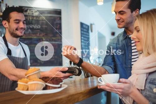 Happy customers with waiter at coffee shop