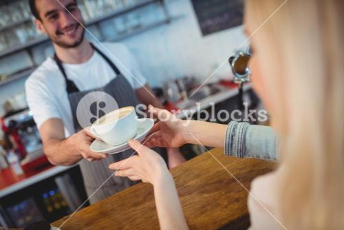 Tilt shot of barista serving coffee to woman at cafe