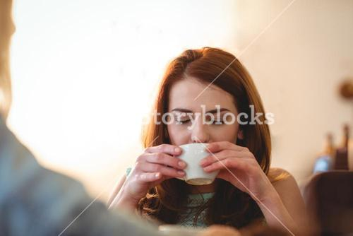 Beautiful woman sipping coffee with friend at cafe