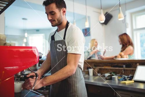 Confident barista using coffee maker at cafe