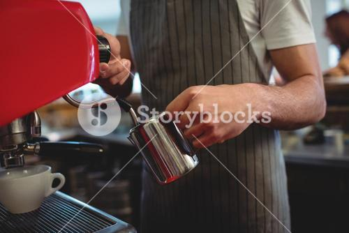Midsection of barista using espresso maker at coffee house