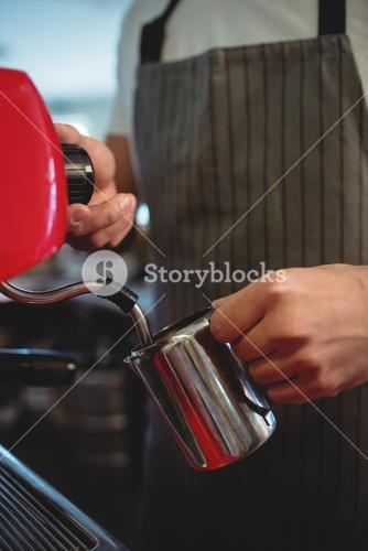 Midsection of barista pouring coffee from espresso maker at cafe