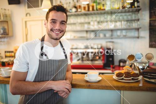 Portrait of happy barista at coffee house