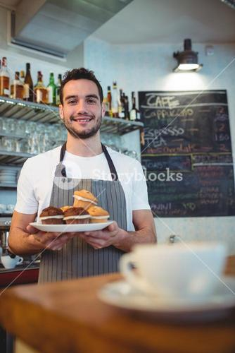 Portrait of confident waiter with cupcakes at coffee house