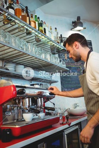 Side view of waiter using coffee maker at cafe