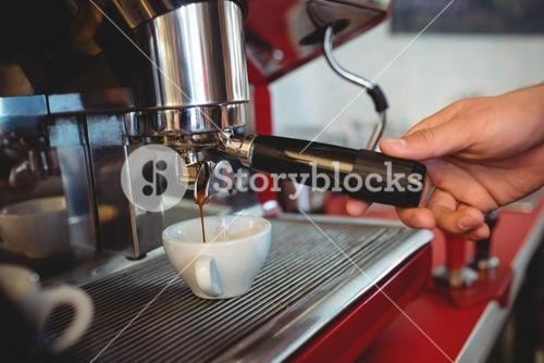 Close-up of waiter holding coffee maker handle at cafe