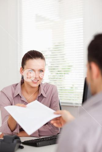 A businesswoman presents a contract to a customer