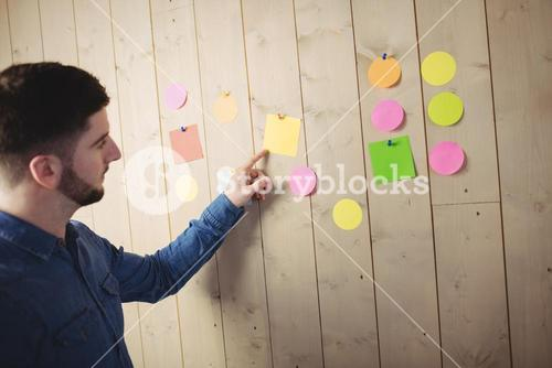 Man pointing at sticky notes