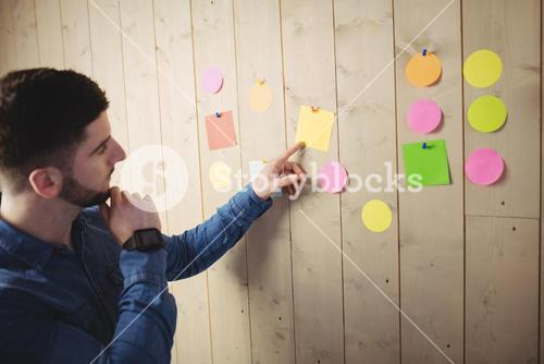 Man looking at sticky notes