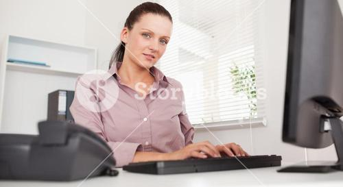 A businesswoman is typing on her keyboard