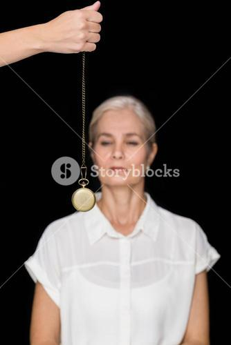 Cropped image of hypnotherapist holding pendulum before woman
