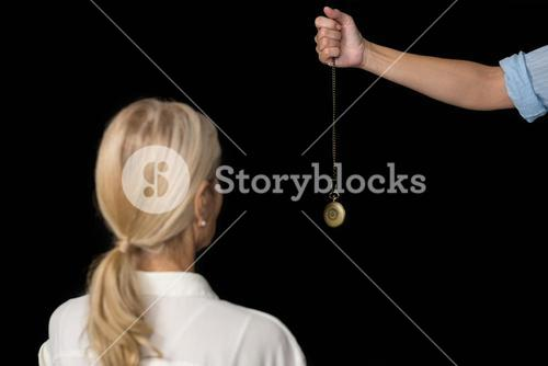Cropped image of hypnotherapist holding pendulum by woman