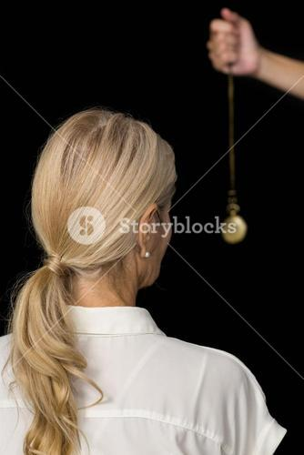Cropped hand of hypnotherapist holding pendulum by woman