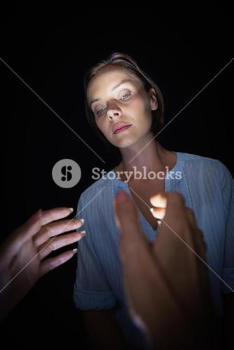 Cropped image of hypnotist hypnotizing woman