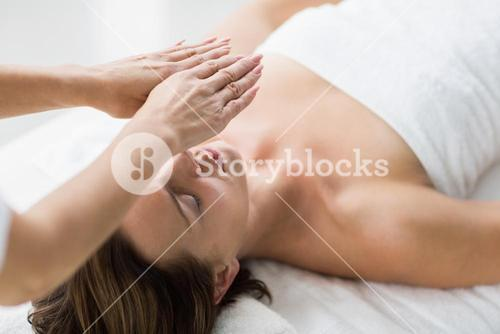 Thearapist performing reiki on woman