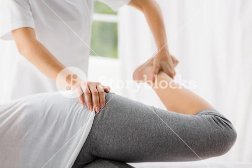 Masseur stretching woman