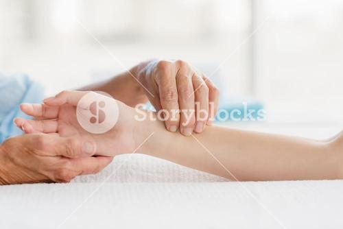 Cropped image of masseur giving hand massage to woman