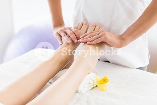 Midsection of masseur giving foot massage to woman