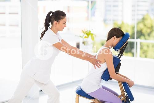 Woman being massaged on chair by masseuse