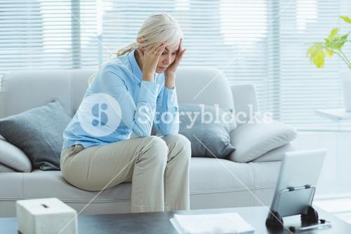 Sad senior woman on sofa