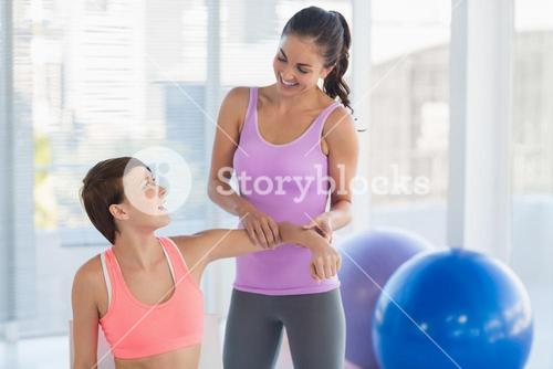 Happy fitness instructor with woman