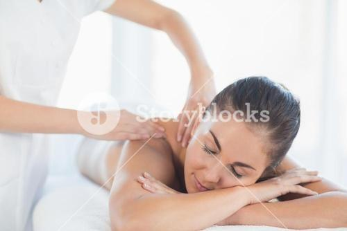 Relaxed woman receiving back massage