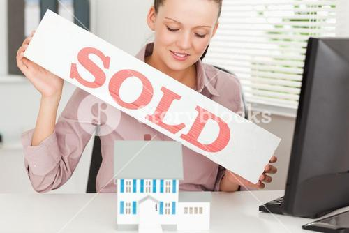 Businesswoman holding a sold sing