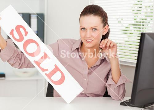 Businesswoman shows sold sign