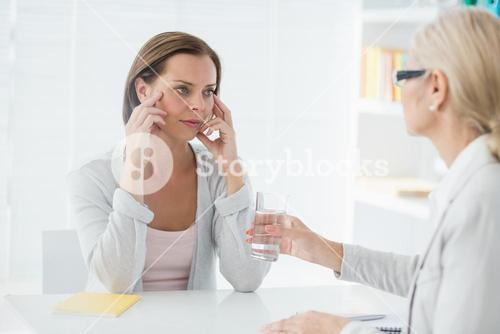 Therapist offering glass of water to her patient