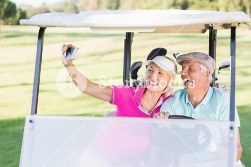 Couple taking selfie while sitting in golf buggy