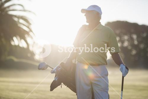 Mature man carrying golf bag while standing on field