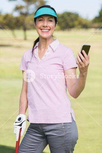 Portrait of smiling golfer woman using phone