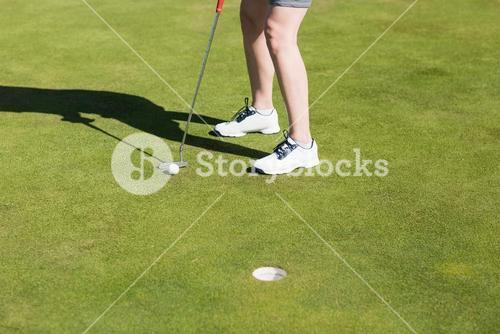 Low section of woman with golf club