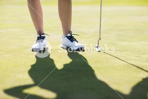 Woman standing with golf club