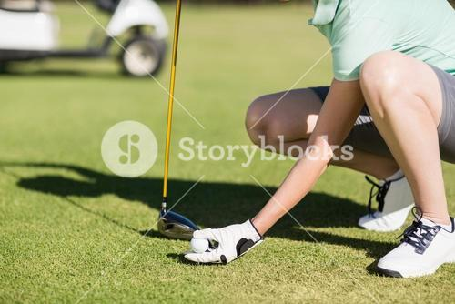 Low section of woman holding golf ball