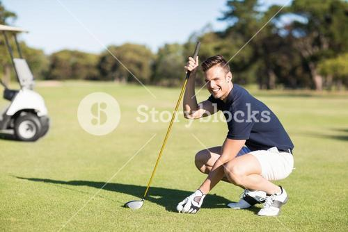 Side view of man placing golf ball on tee