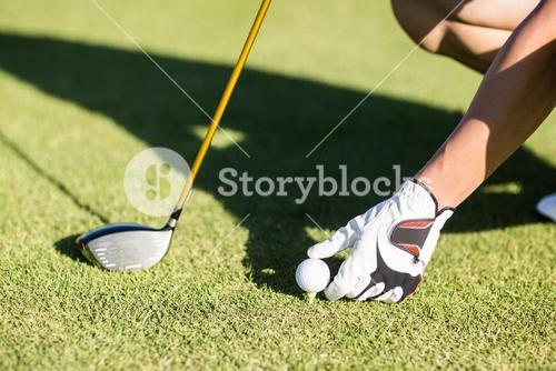 Cropped image of golfer placing golf ball on tee