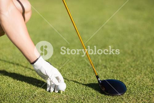 Cropped image of golfer man placing golf ball on tee