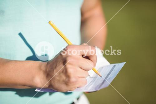 Midsection of golfer with score card