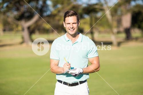 Portrait of smiling golfer with score card